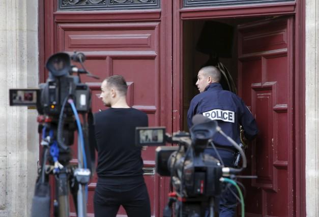 Un policier entre dans l'appartement de Kim Kardashian... (AP, Michel Euler)