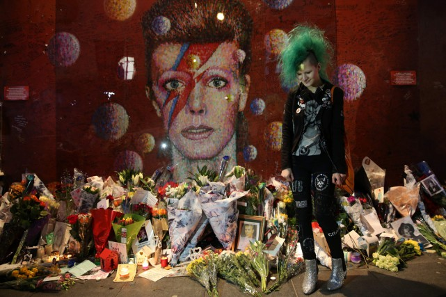 Une fan devant la fresque colorée du chanteur.... (PHOTO AFP)