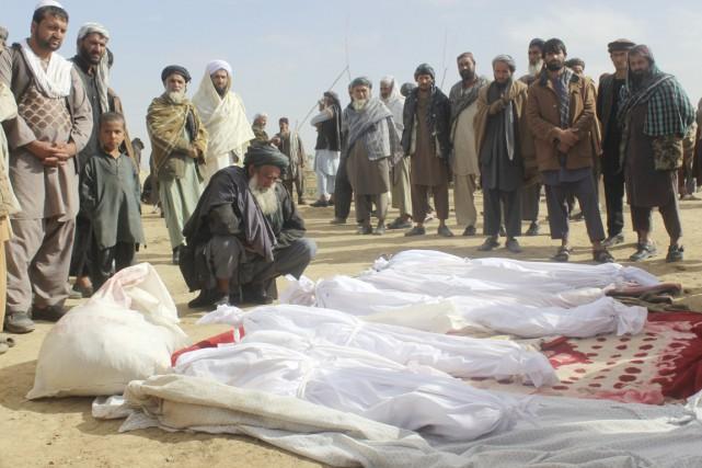 Des villageois sont rassemblés autour des corps de... (photo Najim Rahim, archives AP)