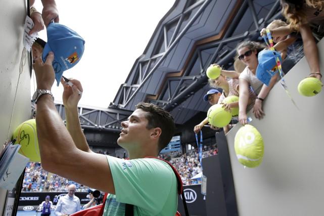 Milos Raonic signe des autographes après sa victoire... (Associated Press)