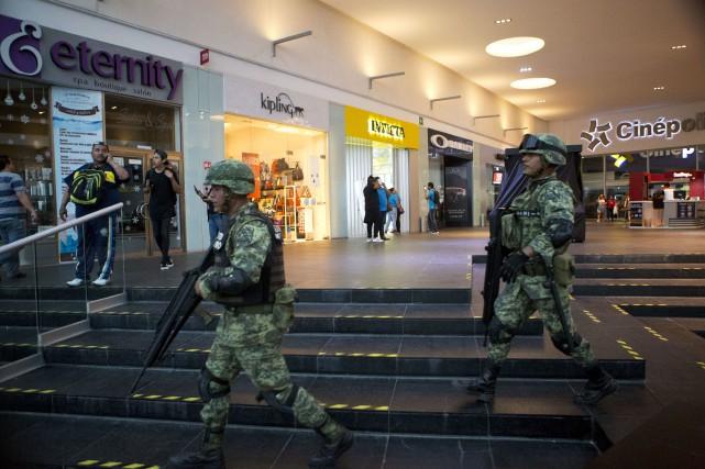Des soldats montent la garde au centre commercialPlaza... (AP, Rebecca Blackwell)