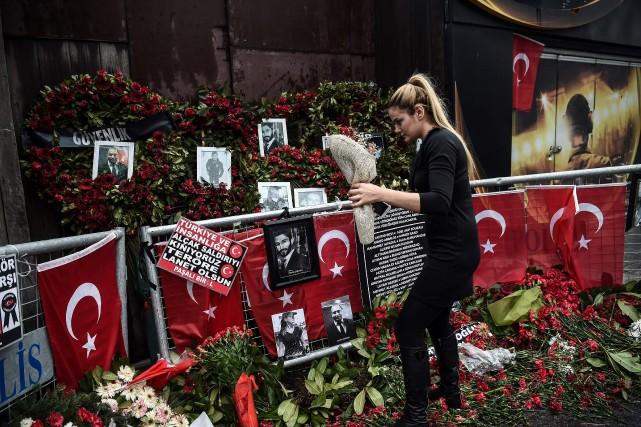 Une femme dépose des fleurs devant la boîte... (PHOTO AFP)