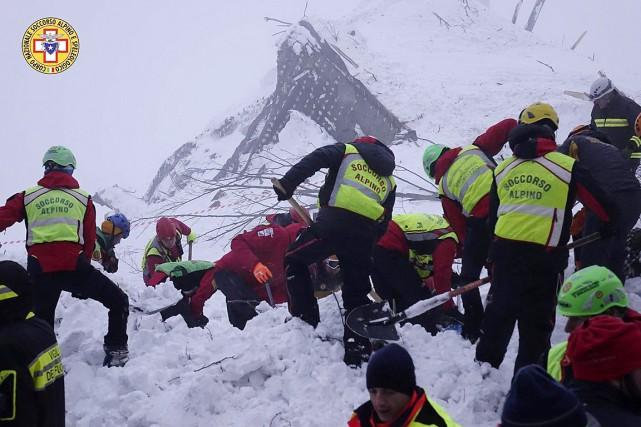 Des secouristes creusent afin de retrouver des survivants... (IMAGE AP/FOURNIE PAR LE CNSAS)