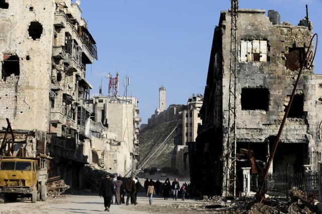 Des civils marchent dans les décombres, à Alep.... (AP, Hassan Ammar)