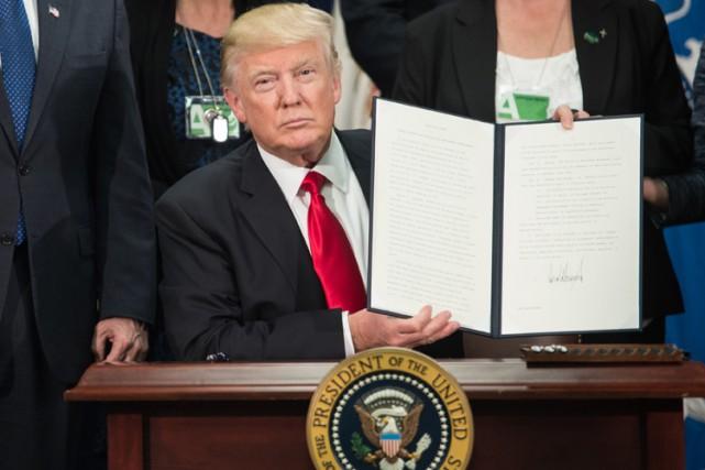 Donald Trump présente aux caméras sa signature sur... (AFP, Nicolas Kamm)