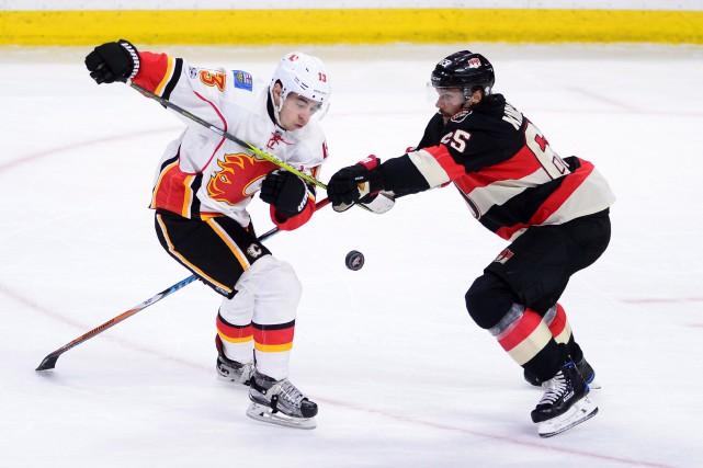 Erik Karlsson (65) tente d'arrêter Johnny Gaudreau (13).... (Photo Sean Kilpatrick, La Presse Canadienne)