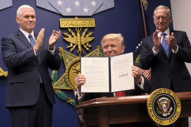 Entouré du vice-président Mike Pence et du secrétaire... (AFP, Mandel Ngan)