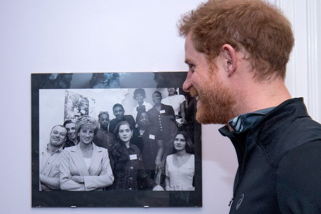 Le prince Harry regarde une photo de sa... (PHOTO GEOFF PUGH, AFP)