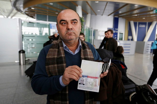 Fuad Sharef Suleman montre son visa américain aux... (PHOTO AHMED SAAD, REUTERS)