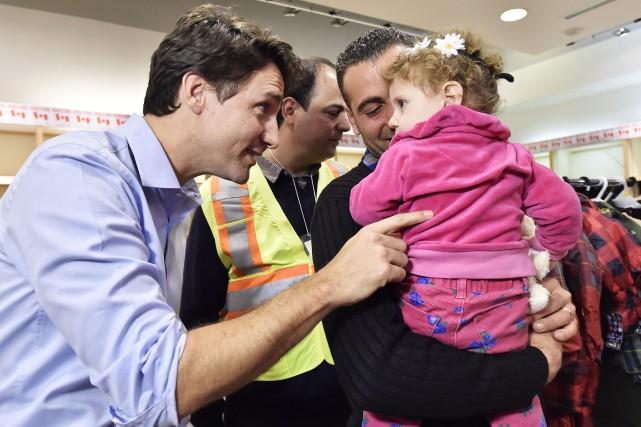 Justin Trudeau accueillant des réfugiés syriens, en décembre... (Photo archives La Presse Canadienne)