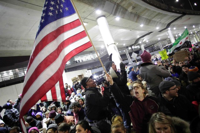 Des manifestants ont envahi l'aéroport de Chicago, brandissant... (Photo AFP)