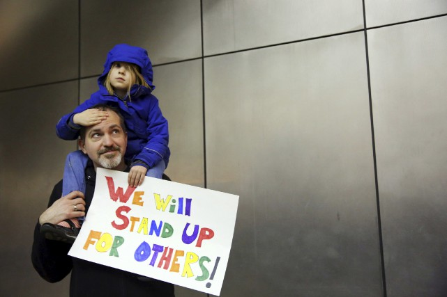 Un père et sa fille manifestent à l'aéroport... (AP)