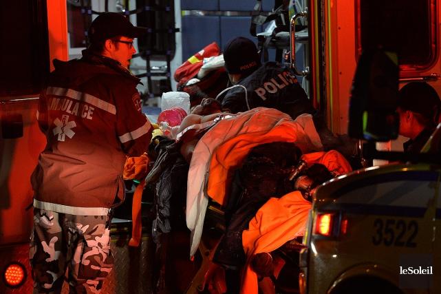 Des ambulanciers évacuent des blessés de la tuerie... (Le Soleil)