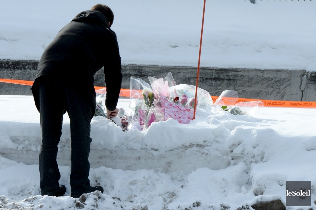 Un homme pose des fleurs près du Centre... (Le Soleil, Erick Labbé)