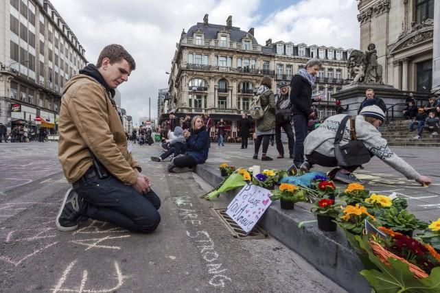 Un homme pleure après avoir déposé des fleurs... (AP, Geert Vanden Wijngaert)