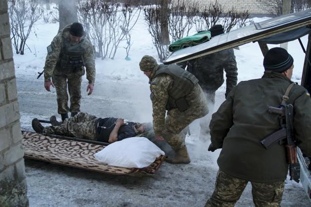 Un soldat ukrainien blessé est transporté sur un... (AP, Inna Varenytsia)