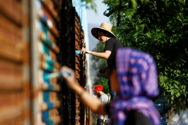 Des artistes peignent le mur à Tijuana.... (PHOTO JOGE DUENES, REUTERS)