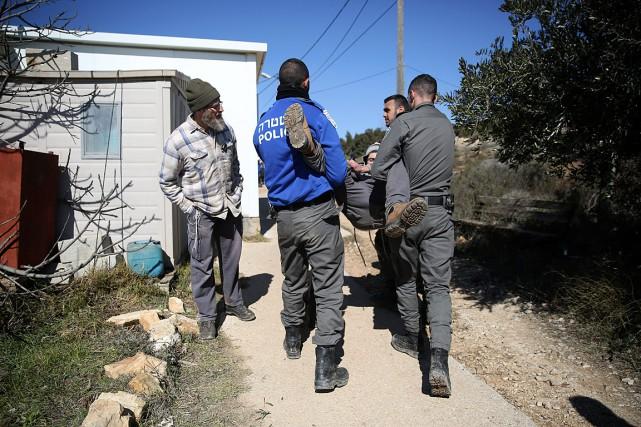 Des policiers israéliens expulsent un homme de la... (Photo Oded Balilty, AP)