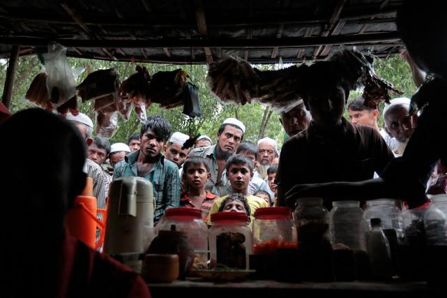 Des Rohingyas regardent une émission de télévision à... (AP)