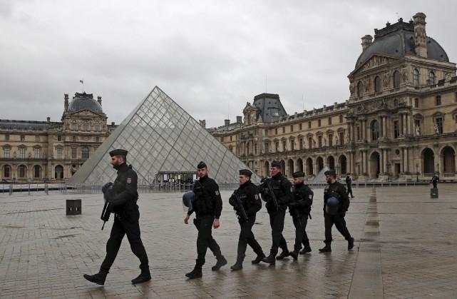 Des policiers patrouillent l'endroit où des soldats ont... (AP, Christophe Ena)