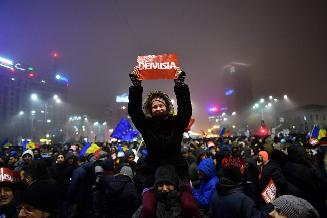 Une jeune femme tient une affiche où il... (PHOTO DANIEL MIHAILESCU, AFP)
