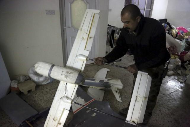Un officier irakien inspecte un drone utilisé par... (AP, Khalid Mohammed)