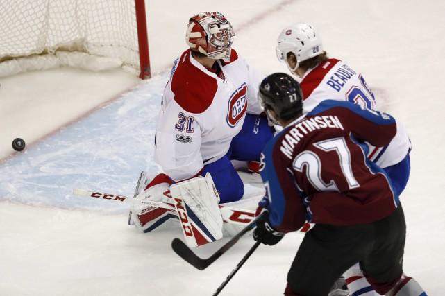 L'attaquant de l'Avalanche Andreas Martinsen regarde la rondelle... (AP, David Zalubowski)