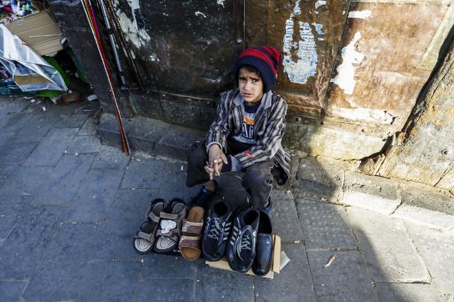 Un enfant vend des souliers dans un marché... (Photo Mohammed Huwais, Agence France-Presse)