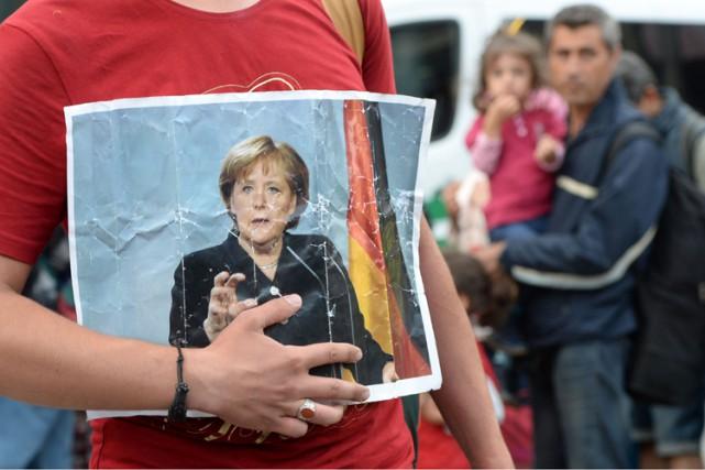 Un réfugié tient une photo d'Angela Merkel à... (ARCHIVES AFP)