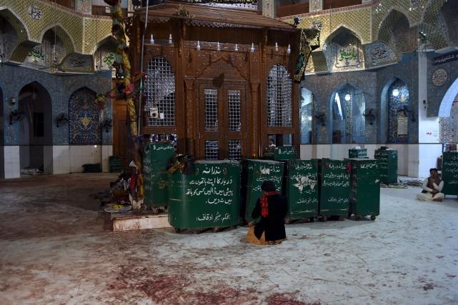 Une fidèle priait sur le plancher encore taché... (AFP, ASIF HASSAN)