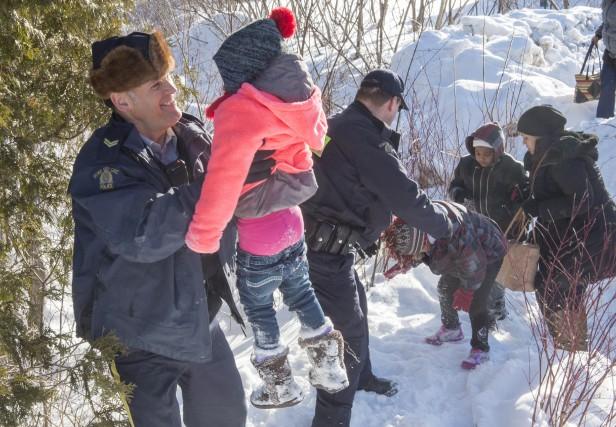 Une famille somalienne est aidée par des policiers... (La Presse canadienne, Paul Chiasson)