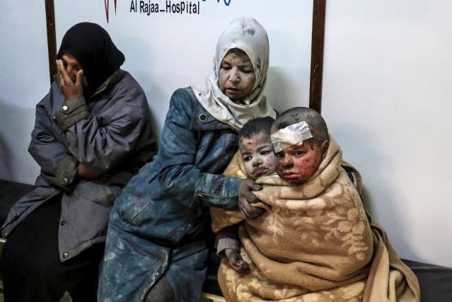 Une femme et ses enfants blessés attendent dans... (AFP)