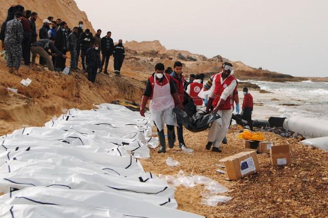 Des bénévoles du Croissant-Rouge libyen récupèrent les cadavres... (AFP, Mohaned Krema)