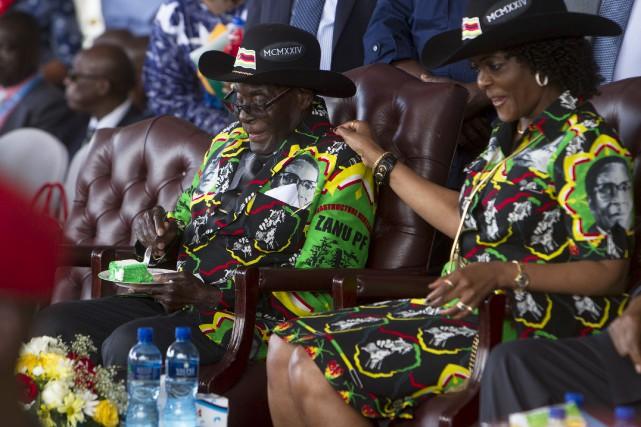 Robert Mugabe, flanqué par sa femme Grace, a... (AP, Tsvangirayi Mukwazhi)