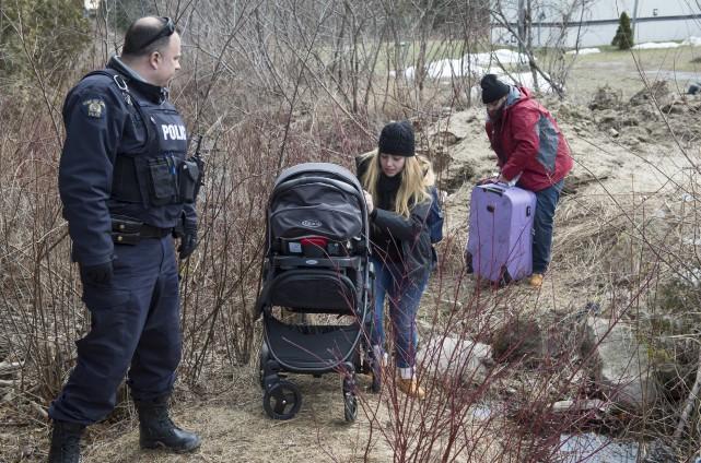 Des réfugiés traversant lundi la frontière canado-américaine à... (Archives La Presse canadienne, Paul Chiasson)