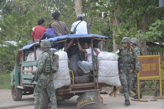 Des militaires inspectent un véhicule dans le sud... (AFP, Nickee Butlangan)