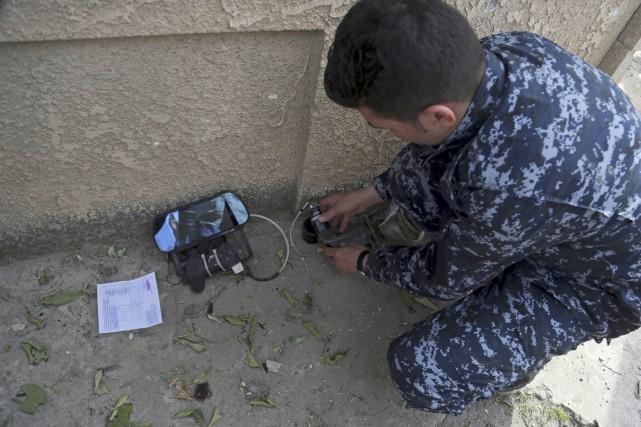Un policier irakien montre un dispositif utilisé par... (AP, Khalid Mohammed)