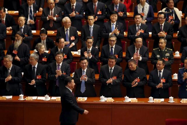 Le président Xi Jinping passe devant des élus,... (AP, Ng Han Guan)