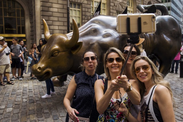 Des touristes visitent Wall Street, à Manhattan.... (ARCHIVES REUTERS)