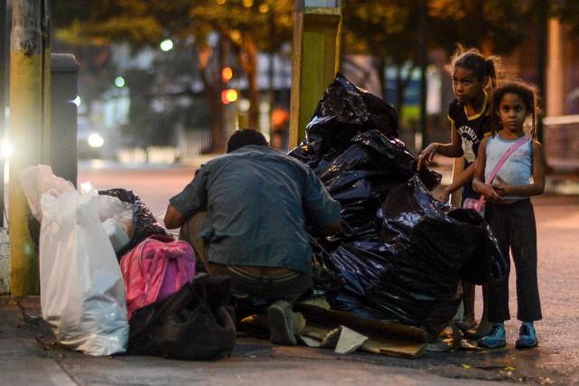 Un père et ses filles fouillent dans les... (AFP, Juan Barreto)