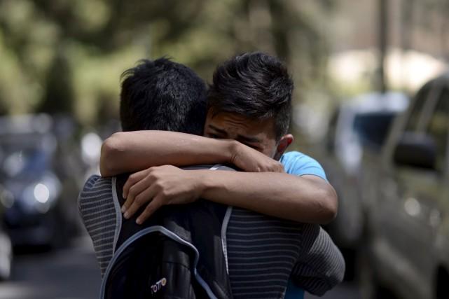 Un survivant étreint un proche après l'incendie mortel... (AFP, Johan Ordonez)