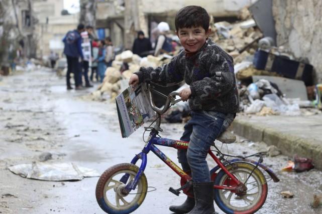 Un petit Syrien près d'Alep tenant un livre... (AP, Khudr Al-Issa)