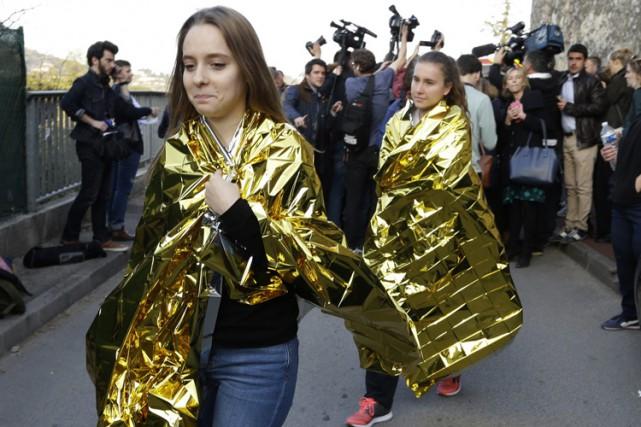 Des jeunes munis de couvertures thermiques sont évacués... (PHOTO AP)