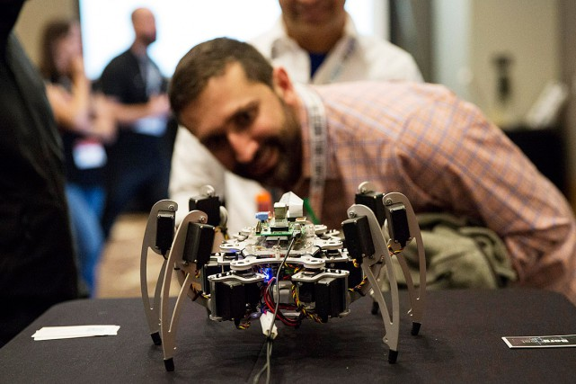 Un visiteur du festival regarde un robot équipé... (Photo Laura Buckman, REUTERS)