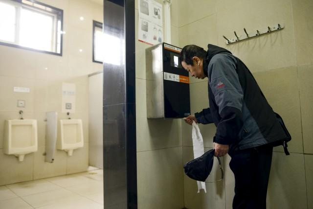 Un Pékinois prend du papier-toilette dans une distributrice... (AFP, WANG Zhao)