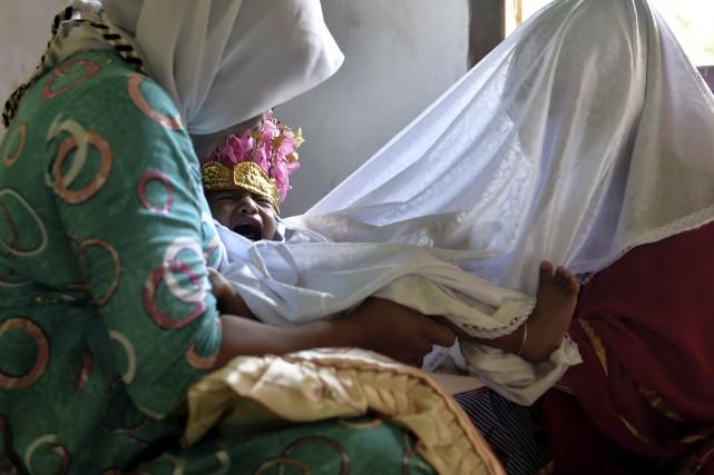 Une guérisseuse recouvre le bébé d'un drap blanc... (AFP, Bay Ismoyo)