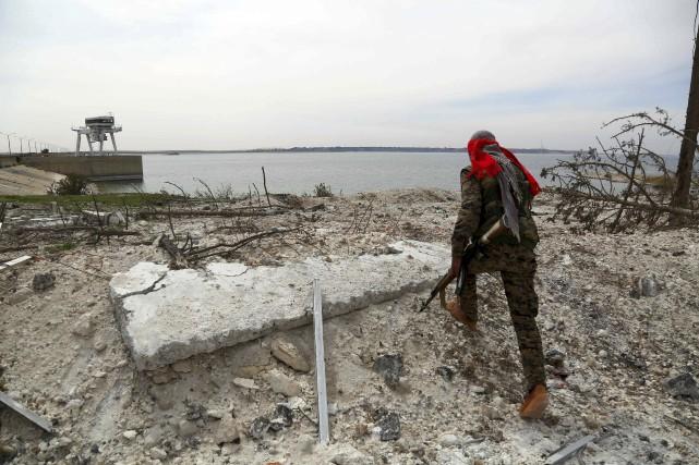 Un membre des Forces démocratiques syriennes inspecte le... (AFP, Delil Souleiman)