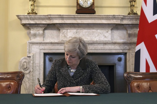 Theresa May signant la lettre officielle qui sera remise... (AP, Christopher furlong)