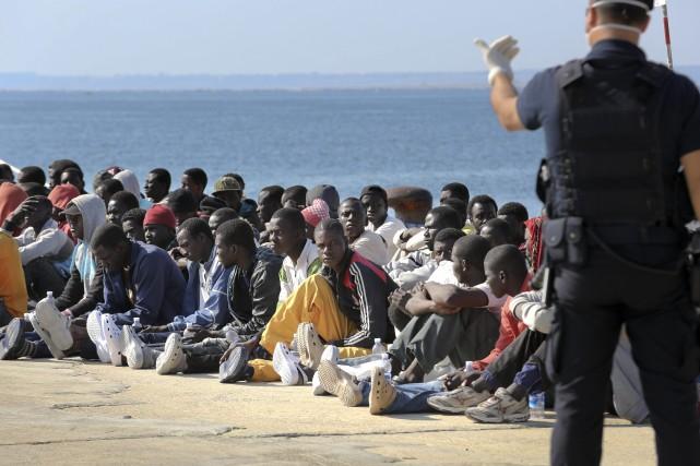 Des migrants sont supervisés par un garde-côte italien... (ARCHIVES AP)