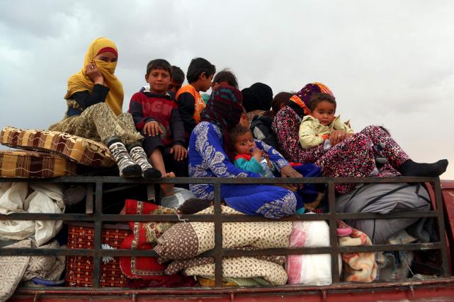 Des réfugiés quittent le village de Suwaidiya, après... (AFP, DELIL SOULEIMAN)